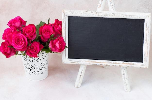 Buquê de rosas brilhantes em um vaso branco e uma placa de escrita