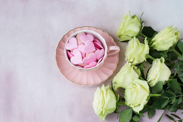 Buquê de rosas claras e corações de cetim em uma caneca rosa