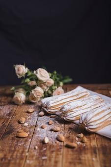 Buquê de rosas com amêndoas e eclairs caseiros no guardanapo sobre a mesa de madeira