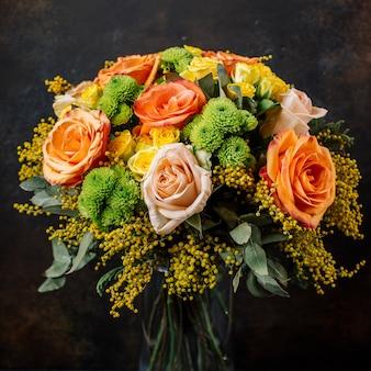 Buquê de rosas com laranja, rosas amarelas, mimosa em fundo escuro