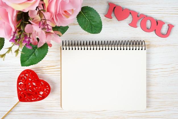 Buquê de rosas cor de rosa e corações do dia dos namorados com o bloco de notas de papel e palavras eu te amo em fundo branco de madeira. vista superior, plano com espaço de cópia