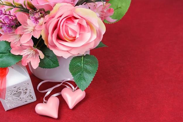 Buquê de rosas cor de rosa e corações do dia dos namorados em fundo vermelho. vista superior, plano com espaço de cópia