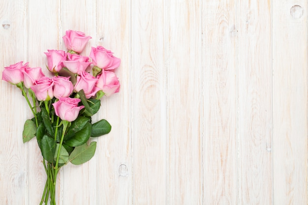 Buquê de rosas cor de rosa sobre a mesa de madeira