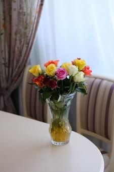 Buquê de rosas de cores diferentes em uma mesa de luz