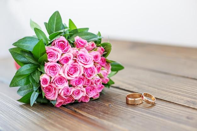 Buquê de rosas e alianças de casamento em uma mesa de madeira.