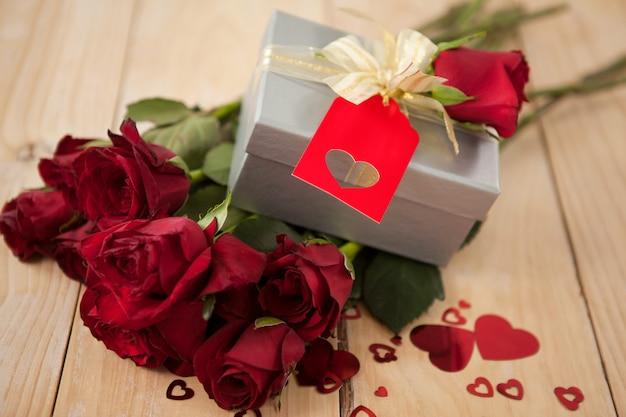 Buquê de rosas e caixa de presente, cercada por decoração de coração