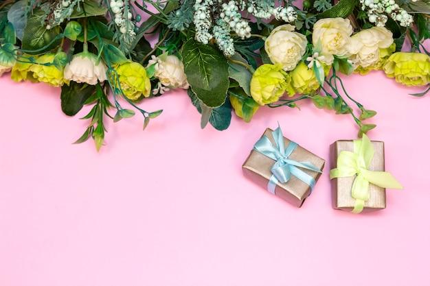 Buquê de rosas e caixas de presente em fundo rosa.