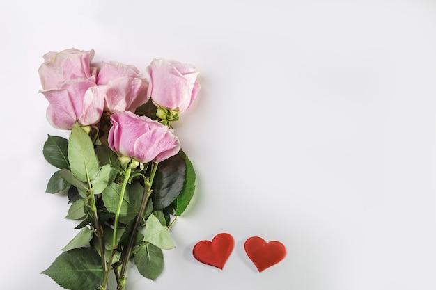 Buquê de rosas e corações em um fundo branco. cartão de dia dos namorados ou banner.