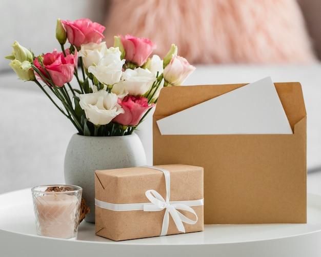 Buquê de rosas em um vaso ao lado de um presente embrulhado e envelope