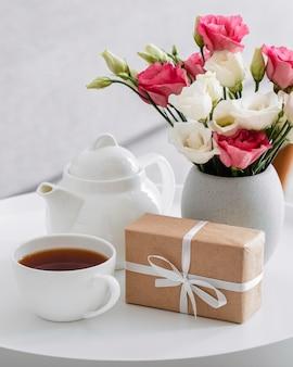 Buquê de rosas em um vaso ao lado de um presente embrulhado e uma xícara de chá