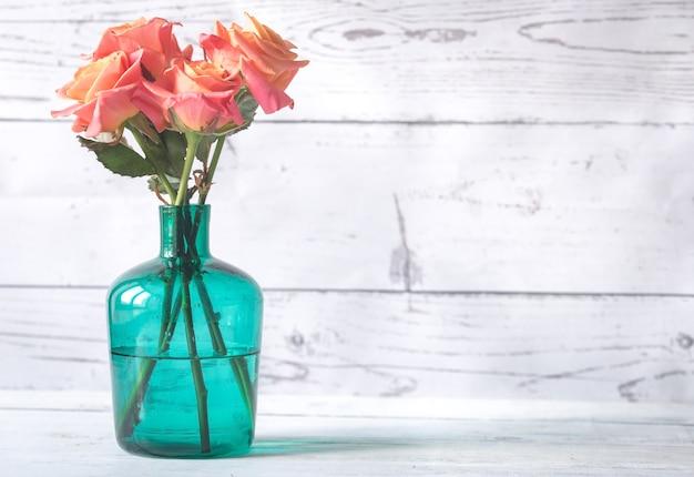 Buquê de rosas em um vaso no fundo de madeira