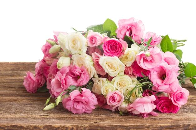Buquê de rosas frescas brancas e rosa e eustoma na borda de madeira isolado