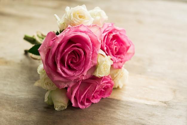 Buquê de rosas frescas em um fundo de madeira