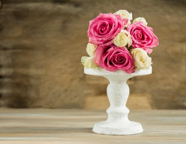 Buquê de rosas frescas em um suporte branco sobre uma mesa