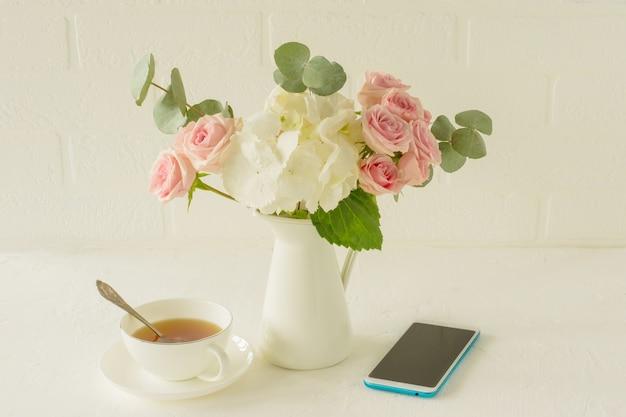Buquê de rosas, hortênsia e eucalipto em uma jarra branca sobre a mesa. composição de flores para decoração de interiores.
