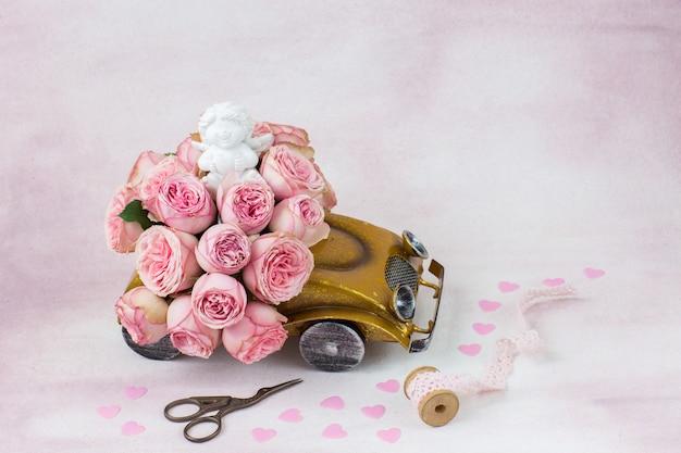 Buquê de rosas no carro, estatueta de um anjo, tesoura, fita de renda e corações rosa