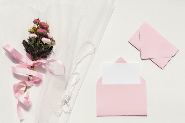 Buquê de rosas no véu ao lado de convites de casamento