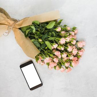 Buquê de rosas rosa embrulhado em papel pardo e smartphone em pano de fundo concreto