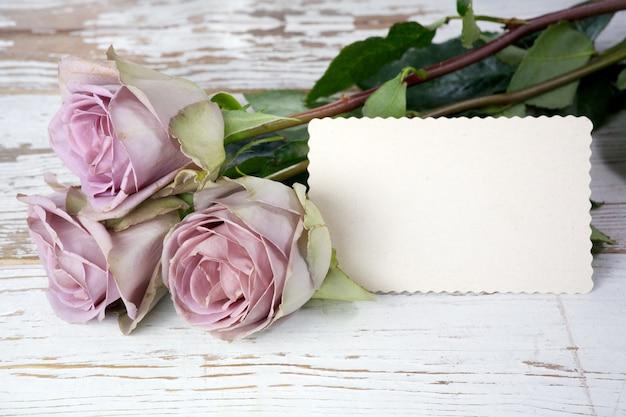 Buquê de rosas roxas e cartão em branco sobre a mesa de madeira.