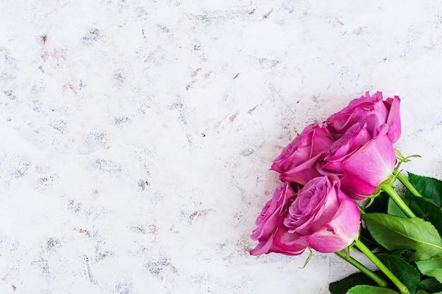 Buquê de rosas roxas em um fundo branco. vista do topo
