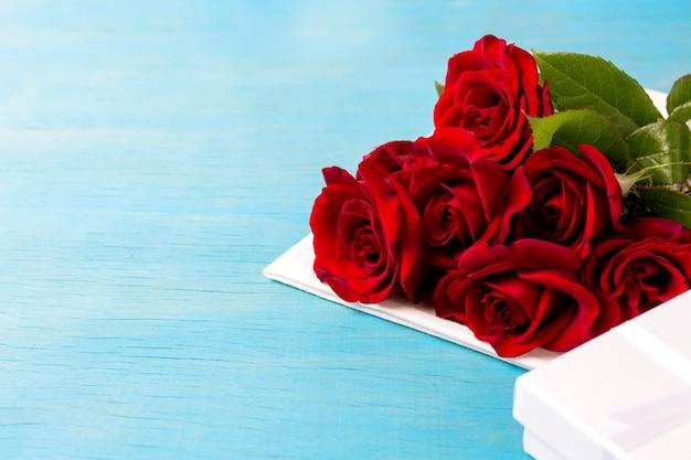 Buquê de rosas vermelhas, caixa de presente branca, fundo de madeira azul. copie o espaço. presente romântico para o feriado do dia dos namorados
