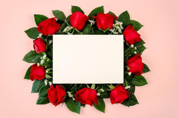 Buquê de rosas vermelhas com cartão de papel branco em branco.