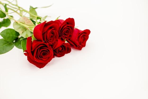 Buquê de rosas vermelhas com uma fita vermelha.