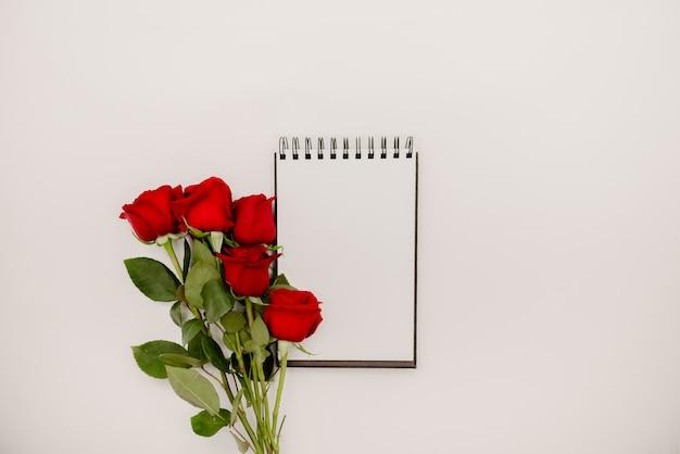 Buquê de rosas vermelhas de flores sobre fundo branco com caderno espiral