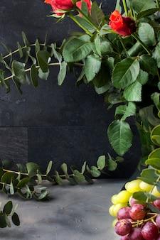 Buquê de rosas vermelhas e muitas folhas verdes em um vaso em um fundo preto