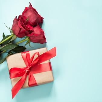 Buquê de rosas vermelhas e presente em azul. cartão do dia dos namorados. copie o espaço.