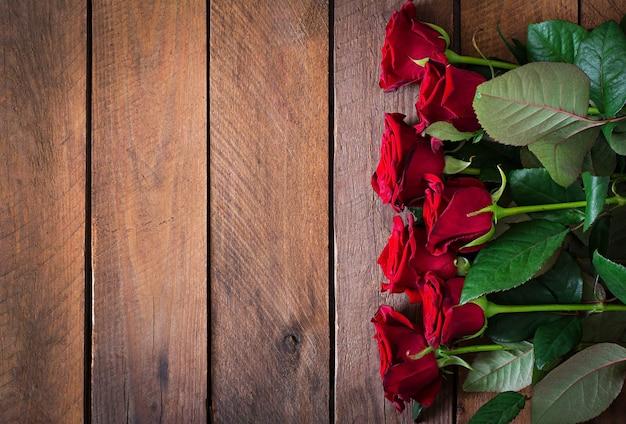 Buquê de rosas vermelhas em fundo de mesa de madeira