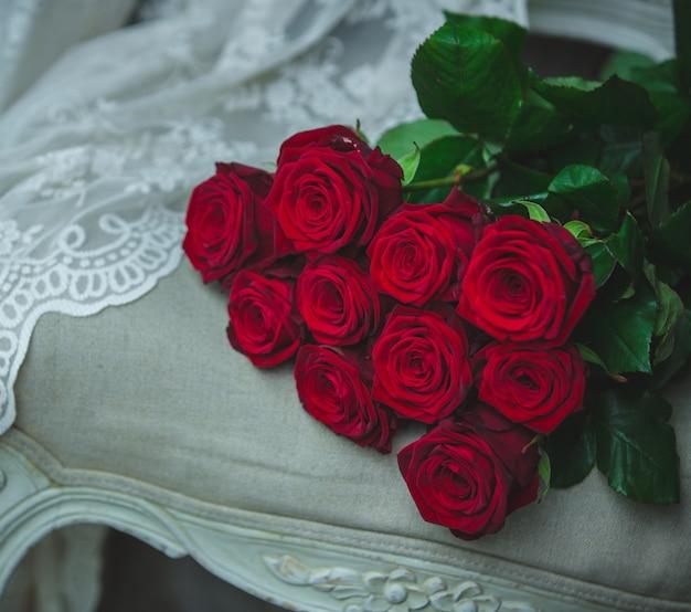 Buquê de rosas vermelhas em pé em uma cadeira de cor bege com detalhes de cortina.