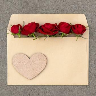 Buquê de rosas vermelhas em um envelope com um coração. cartão postal com lugar para design.
