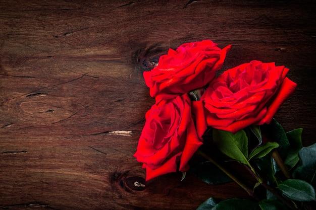 Buquê de rosas vermelhas em um fundo de madeira texturizado, espaço livre para texto