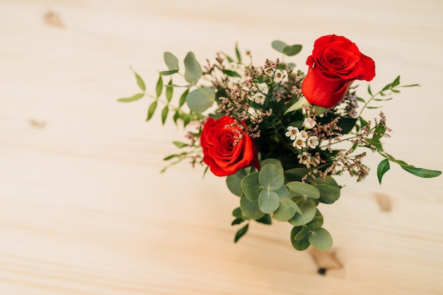 Buquê de rosas vermelhas em um vaso rosa em uma mesa de madeira