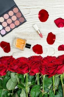 Buquê de rosas vermelhas, paleta de perfume, batom e sombra sobre uma mesa de madeira branca. vista do topo