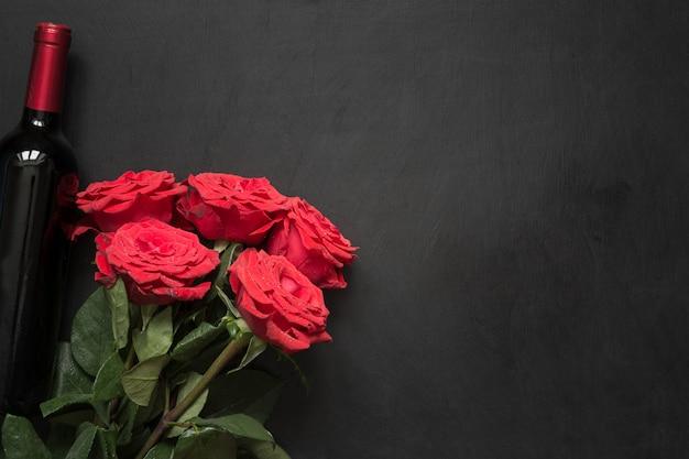Buquê de rosas vermelhas românticas, garrafa de vinho tinto na mesa preta.