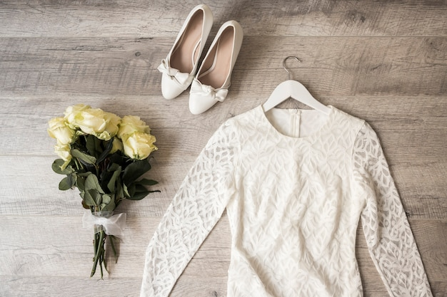 Buquê de rosas; vestido de casamento; e sapatos no pano de fundo de madeira