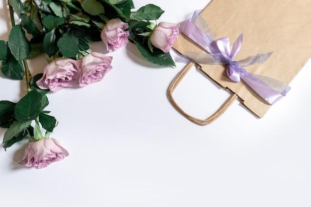 Buquê de rosas violetas com sacola de compras em fundo branco, vista superior, espaço de cópia.