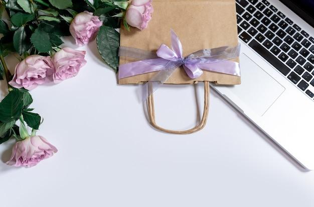 Buquê de rosas violetas e laptop com sacola de compras em fundo branco, vista superior, copie o espaço.