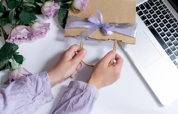 Buquê de rosas violetas, laptop e mãos de mulher com sacola de compras no fundo branco, vista superior, copie o espaço.