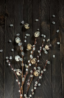 Buquê de salgueiro com flores e ovos de codorna em um fundo escuro de madeira