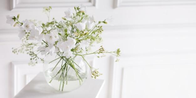 Buquê de sinos suaves em vaso. luz da manhã na sala. decoração suave, vaso de vidro com flores brancas sobre fundo branco da parede e mesa de madeira. interior. cartão de felicitações copie o espaço. bandeira