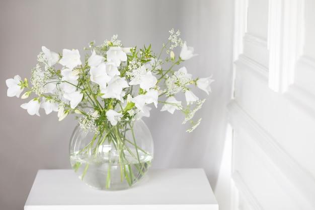 Buquê de sinos suaves em vaso. luz da manhã na sala. decoração suave, vaso de vidro com flores brancas sobre fundo branco da parede e mesa de madeira. interior. cartão de felicitações copie o espaço.
