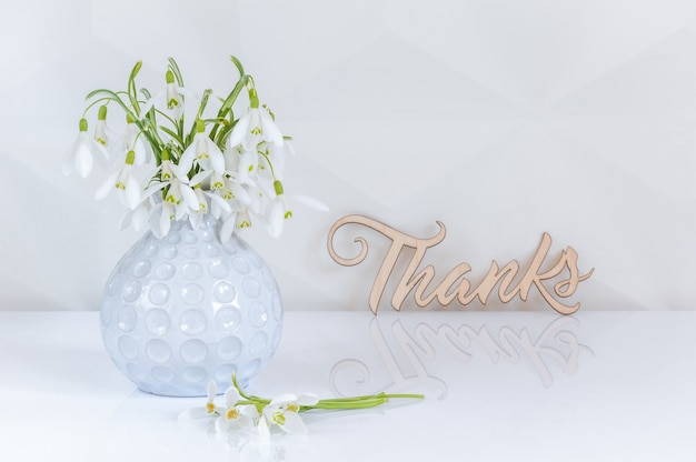 Buquê de snowdrops no vaso na mesa de vidro e fundo branco