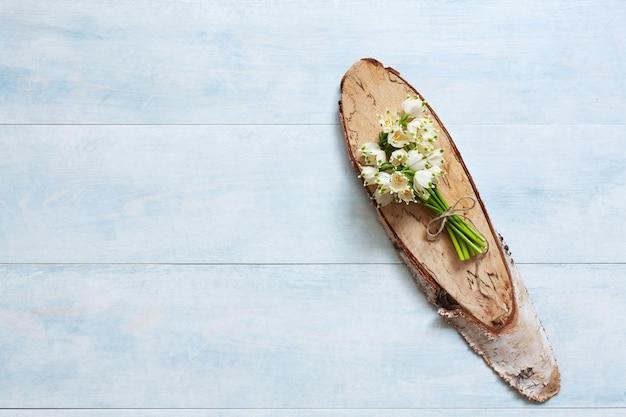 Buquê de snowdrops sobre um fundo de madeira azul claro