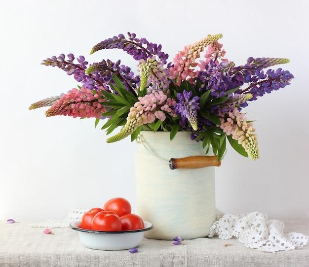 Buquê de tremoços em uma lata e tomates. natureza morta com flores na mesa.