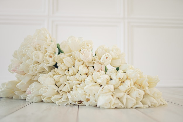 Buquê de tulipa branca enorme no chão de madeira branco. espaço de páscoa, espaço de cópia