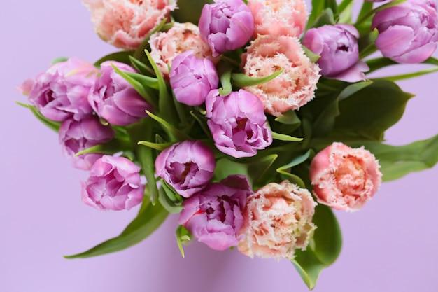 Buquê de tulipa. tulipas em uma superfície suavemente roxa. buquê de flores de tulipas terry lilás e rosa
