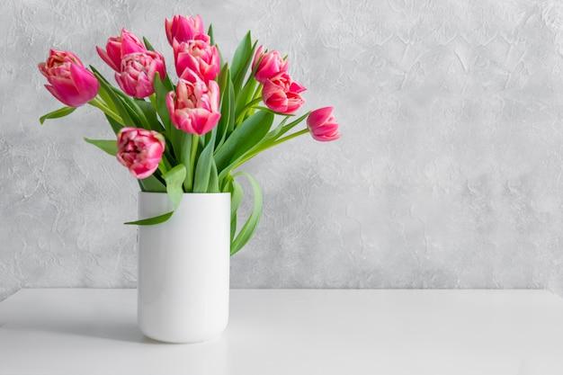 Buquê de tulipa vermelha em um vaso na mesa branca vintage.